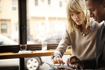 Couple using digital tablet while sitting in cafe