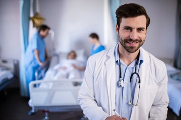 Smiling male doctor standing in hospital