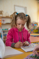 A small pre-school girl with pigtails draws in colored pencils in a kindergarten. preschool education