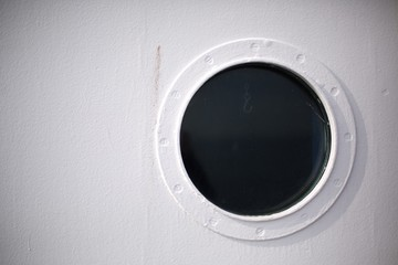 White boat with round dark porthole window with hanging chain hook