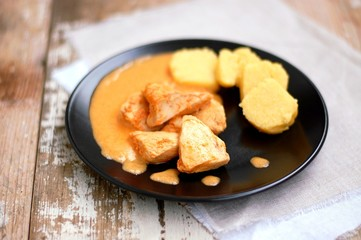Chicken fillet on sweet pepper with creamy sauce with polenta dumplings on black plate on wooden background