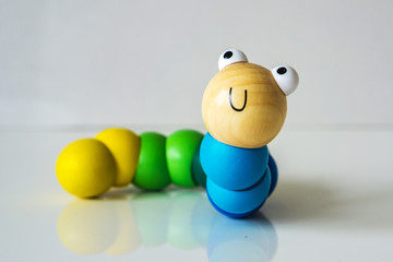 Closeup of wood, colorful, kids, toy caterpillar on the white background, suitable for babies and children up to 1 year. Concept motor.