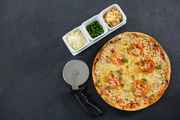 Pizza with pizza cutter and ingredients