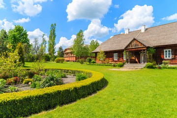 Wall Mural - Old traditional manor house and beautiful garden in Tokarnia village on sunny spring day, Poland