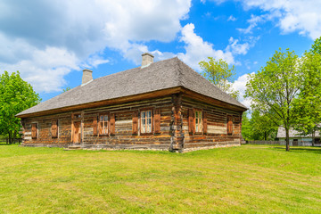Old traditional wooden house in Tokarnia village on sunny spring day, Poland