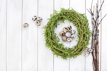 Easter composition of quail eggs in a nest with a pussy-willow on a white wooden background. Holiday concept with copy space view from above.