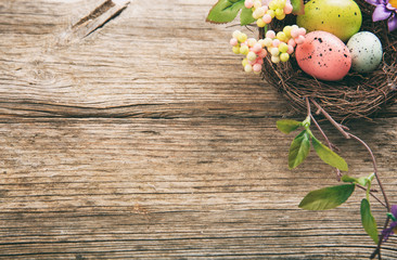 Colorful Easter eggs and copy space on wooden background
