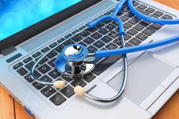 Stethoscope and laptop on a wooden table. Medical help online