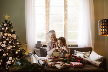 Grandmother and granddaughter wrapping Christmas gifts