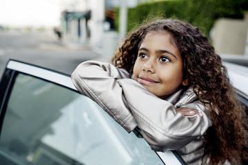Girl leaning against car door, smiling