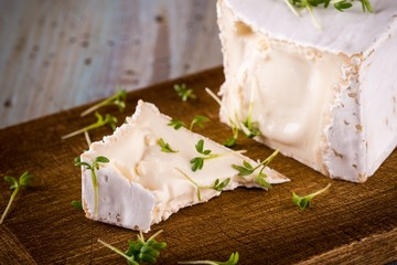 Unusual Camembert cheese with cube shape with spilled green cress on wooden board