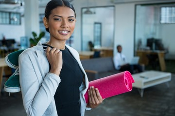 Businesswoman holding exercise mat and shoes smiling at camera