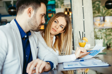 Young business woman and man at a meeting in a cafe looking at paperwork