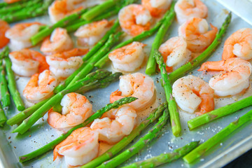 Fresh asparagus with shrimp on a baking sheet with coarse salt, olive oil and black pepper