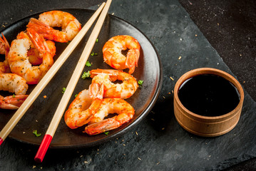 Seafood. Shellfish. Fried grilled shrimp prawns on wooden skewers, with soy sauce, asian style. Snack, appetizer. On black concrete table, copy space
