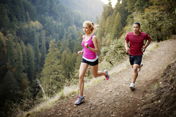 Two young people jogging in forest