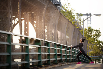 Young woman stretching on footbridge