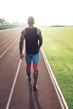 Sportsman walking along running track on stadium, rear view
