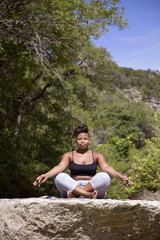 Young woman meditating on rock