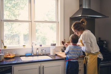 Little boy helping mother in kitchen