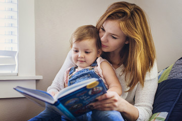 Mother reading book to little daughter
