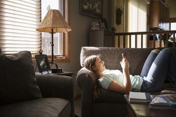 Teenage girl (16-17) lying on sofa and using cell phone