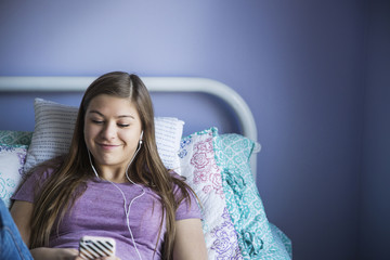 Teenage girl (16-17) lying on bed and listening music on smartphone