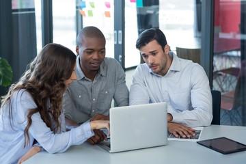 Team of graphic designers discussing over laptop