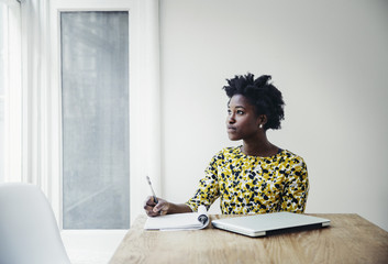 Businesswoman writing at table