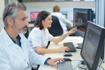 Team of medical analysts working on computers
