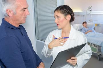 Nurse talking to man outside patient's room