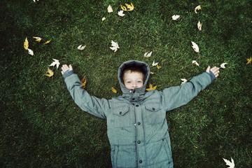 Portrait of boy (6-7) lying in field