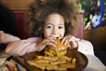 Portrait of girl eating hamburger in restaurant