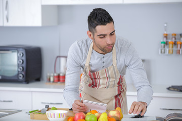 young handsome man preparing lunch in kitchen