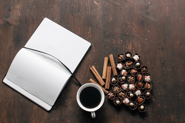 Cup of coffee with chocolate candies and a Notepad on wooden background. Work and relax space concept