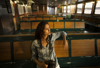 Female sitting on wooden sit in empty tourboat looking at view