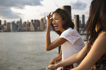 Young woman laughing with city skyline in background