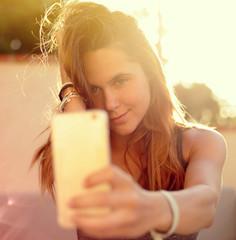 Belle jeune femme prenant un selfie au soleil