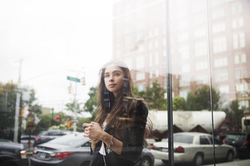 Young woman with mobile phone reflecting in shop window