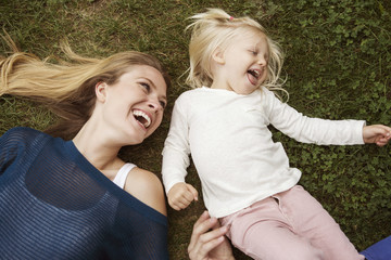 Woman lying on grass with girl (2-3)