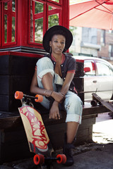 Young female wearing hat sitting on street bench with skateboard red construction and sunshade in background