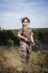 Girl (6-7) holding hunting rifle