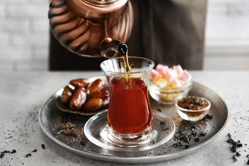 Pouring Turkish tea into traditional glass and sweets on metal tray closeup