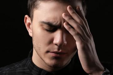Handsome depressed man on black background
