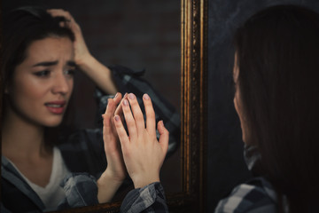 Depressed young woman looking on her reflection in mirror