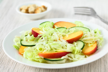 Fresh nectarine, cucumber and iceberg lettuce salad on plate, photographed with natural light (Selective Focus, Focus in the middle of the salad)