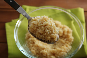 Spoon with boiled sprouted organic white quinoa grains, close up