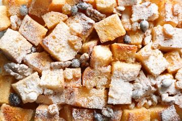 Fresh bread pudding with raisins, walnuts and sugar powder, closeup