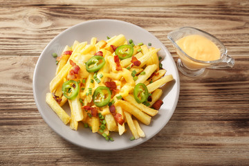 Tasty cheese fries with sliced pepper and sauce on wooden table