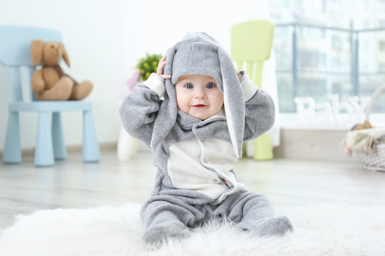 Cute little baby in bunny costume sitting on furry rug at home